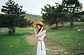 Woman wearing sun hat standing in field