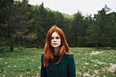 Serious Caucasian woman wearing coat in field
