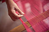 Hand of Hispanic woman weaving fabric on loom