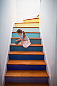 Caucasian girl using digital tablet on multicolor staircase
