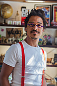 Serious mixed race man wearing suspenders