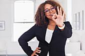 Mixed race woman gesturing okay in gallery