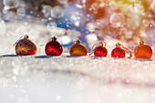 Row of Christmas ornaments in the snow