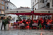 People sit underneath heat lamps outside No Stress Bistro and enjoy lunch on a rainy afternoon, Split, Split-Dalmatia, Croatia