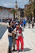 Asian couple take selfie photograph with smartphone and selfie stick on seafront promenade, Split, Split-Dalmatia, Croatia