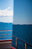 Window reflection of sailboat in Adriatic Sea seen from aboard cruise ship MS Romantic Star (Reisebüro Mittelthurgau), near Split, Split-Dalmatia, Croatia