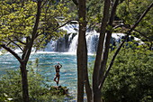 Young woman performs yoga in front of waterfalls at Krka National Park, near Skradin, Šibenik-Knin, Croatia