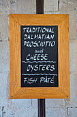 Menu board at restaurant advertises traditional Dalmatian prosciutto and cheese, oysters and fish paté, Trogir, Split-Dalmatia, Croatia