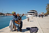 Street musician plays guitar and performs along seafront promenade with cruise ship MS Romantic Star (Reisebüro Mittelthurgau) behind, Trogir, Split-Dalmatia, Croatia