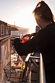 Waitress with tray of drinks that were lifted with pulley from bar to rooftop of Massimo Cocktail Bar located in old fortress tower in Old Town, Korcula, Dubrovnik-Neretva, Croatia