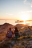 Couple admires view across Lapad Peninsula and islands seen from hillside near top of Dubrovnik Gondola at sunset, Dubrovnik, Dubrovnik-Neretva, Croatia