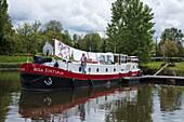 Flusskahn Bella Fortuna liegt am Yachthafen Port de Savoyeux am Fluss Petit Saône, Eigentümer hängt Wäsche zum trocknen auf, Seveux, Haute-Saône, Bourgogne Franche-Comté (Burgund), Frankreich, Europa