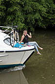 Woman sits on bow of Le Boat Magnifique houseboat during cruise on Petit Saône river and raises glass of wine, near Soing, Soing-Cubry-Charentenay, Haute-Saône, Bourgogne-Franche-Comté, France