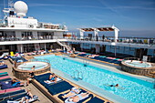 People enjoy a sunny afternoon on Pooldeck of cruise ship MS Mein Schiff 6 (TUI Cruises), Baltic Sea, near Rønne, Bornholm, Denmark