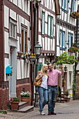 Couple enjoys stroll through Altstadt old town with half-timbered houses, Bad Orb, Spessart-Mainland, Hesse, Germany