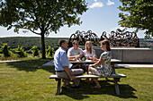 'Menschen sitzen an Picknicktisch vor der ''Wein & Bibel''-Skulptur (nach dem letzten Abendmahl) am Terroir F-Standort am Kapellenberg, Frickenhausen, nahe Ochsenfurt, Fränkisches Weinland, Franken, Bayern, Deutschland, Europa'