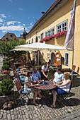 People sit outside and enjoy lunch on terrace of restaurant, Frickenhausen, near Ochsenfurt, Franconia, Bavaria, Germany