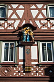 Religious sculpture on half-timbered house in Altstadt old town, Miltenberg, Spessart-Mainland, Franconia, Bavaria, Germany