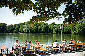 In the beer garden at the Seehaus in the English Garden in Munich, Bavaria, patrons are seated right at the lake