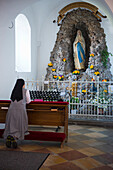 a nun is praying in a side chappel in the church of the Mallersdorf Monastery in Lower Bavaria