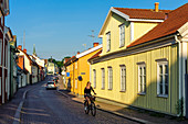 Young woman is cycling in alleys of Vimmerby, Sweden