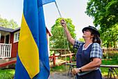 Swedish allotment garden in the open-air museum Skansen, the Swedish flag is overtaken, Stockholm, Sweden