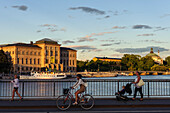 Pedestrian and cyclist in front of National Museum, Stockholm, Sweden