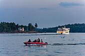 Young people in motorboat in Vaxholm, Stockholm, Sweden
