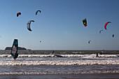 in the background, mogador island, kitesurfing, windsurfing and water sports on taghart beach, essaouira, mogador, atlantic ocean, morocco, africa