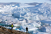 tourists in front of the spectacle that is the river of ice, jakobshavn glacier, 65 kilometres long, coming from the inlandsis, sermeq kujalleq, ilulissat, greenland
