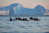 kayaking at nightfall in front of the icebergs in the ice fjord, jakobshavn glacier, 65 kilometres long, coming from the inlandsis, sermeq kujalleq, ilulissat, greenland