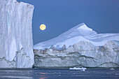 after the sunset, the moon rising over the icebergs in the ice fjord, jakobshavn glacier, 65 kilometres long, coming from the inlandsis, sermeq kujalleq, ilulissat, greenland