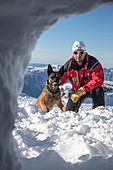 jean-michel morlot and his belgian malinois named jeep in front of an opening in the snow looking for a victim, reporting on avalanche dog handlers, training organized by the anena with the approval of the civil security department, les-2-alpes (38), fran