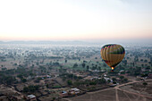 Hot air balloon in the early morning, flying over countryside and the village of Samode, Rajasthan, India, Asia