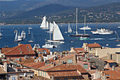 France, Var department, a large view on the old roofs of the city of Saint-Tropez with in background yachting boats