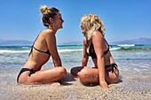 Two happy young women sitting together on the beach, Dutch ethnicity, At holiday destination Chrissi Island, Crete, Greece