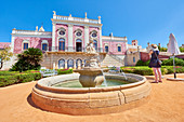 A tourist takes a photo at the entrance of Estoi Palace, in the Algarve, Portugal, Europe