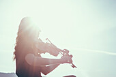 Low angle view of woman playing violin against sky on sunny day