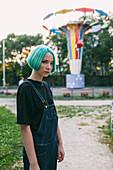 Portrait of teenage girl standing against amusement park ride