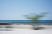Blurred motion view of beach against clear sky