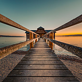 on the jetty to the boathouse during a romantic sunset, Stegen, Bavaria, Germany