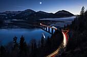 lighttrails of cars crossing the Faller-Klamm-bridge at the Sylvensteinspeicher, Lenggries, Bavaria, Germany