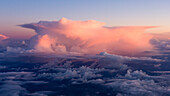 a thunderstorm is painted in pink light during sunset