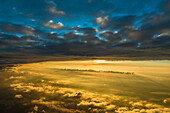 a thin layer of clouds devides the blue sky from the warm light of the sunset, aerial shot