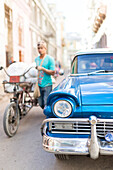 Rickshaw cycle next to a blue oldtimer, street scene, historic town center, old town, Habana Vieja, Havana, Cuba, Caribbean island