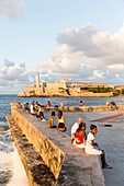 Tourists and local people and fisherman at Malecon, historic town center, old town, Habana Vieja, Habana Centro, opposite Castillo De Los Tres Reyes Del Morro, family travel to Cuba, holiday, time-out, adventure, Havana, Cuba, Caribbean island