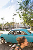 blue oldtimer driving along Central Park, parque central, historic town, center, old town, Habana Vieja, Habana Centro, family travel to Cuba, holiday, time-out, adventure, Havana, Cuba, Caribbean island