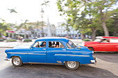 blue and red oldtimer driving along Central Park, parque central, historic town, center, old town, Habana Vieja, Habana Centro, family travel to Cuba, holiday, time-out, adventure, Havana, Cuba, Caribbean island