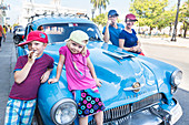 family standing in front of an blue oldtimer, pretending to smoke a cigar, at park Parque Jose Marti in the center of Cienfuegos, colonial town, family travel to Cuba, parental leave, holiday, time-out, adventure, MR, Cienfuegos, Cuba, Caribbean island