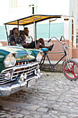 bicycle rickshaw, young cool boys taking a rest, oldtimer, center of the city, family travel to Cuba, parental leave, holiday, time-out, adventure, Trinidad, province Sancti Spiritus, Cuba, Caribbean island
